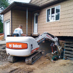 Excavating to expose the foundation walls and footings for a replacement job in Marion