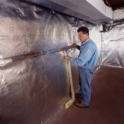 Installation of a radiant heat and vapor barrier on a basement wall in Galax